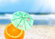 Orange cocktail. With an umbrella on the beach, blurred background Stock Photography
