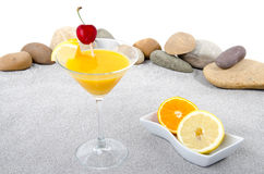 Orange cocktail on a background of sand and pebble stones Stock Image