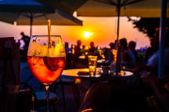 Orange cocktail in a beach bar at the sunset. A glass of cold orange cocktail at the sunset on the table of a beach bar at the sunset, with blurry people arround Stock Photo