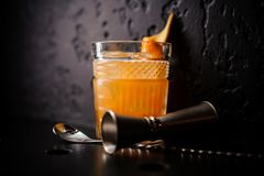 Orange cocktail in crystal glass with bar spoon and jigger Royalty Free Stock Photography