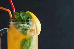 Orange Cocktail im Glasgefäß auf schwarzem Hintergrund Stockbilder