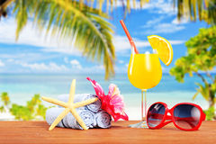 Orange cocktail and other summer accessories on a table with pal Stock Photos