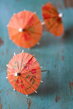Orange cocktail paper umbrellas. On blue rustic wood table stock images