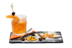 Orange coctail with cinnamon sticks. Orange coctail in the glass and beautiful serving dishes with cinnamon sticks, oranges and small candies in isolated white Stock Image