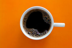 Orange coffee. Cup with the coffee against the orange background Royalty Free Stock Photo