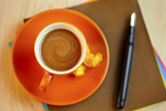 Orange coffee cup on brown writing paper with pen Stock Image