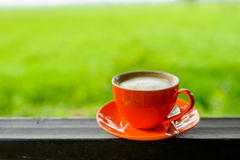 Orange coffee cup with nature bokeh Stock Image