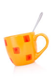 Orange coffee cup with a spoon Stock Images
