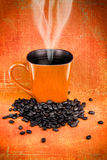 Orange coffee mugs and coffee beans Royalty Free Stock Images