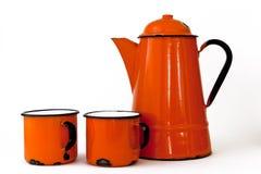 Orange  coffee pot and mugs. A orange enamel coffee pot with two coffee mugs Stock Photos