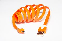 Orange coiled USB cable. Coiled USB cable. Orange color. Orange micro USB data and power cable for smartphones.  on white background Stock Photo