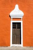 Orange Colonial Building in Valladolid. Old wooden door on an orange colonial building in the historic center of Valladolid, Mexico Stock Photos