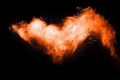 Orange color powder explosion on black background. Mauve orange color cloud. Orange dust splash in the air. Freeze motion orange color paint Holi royalty free stock photos