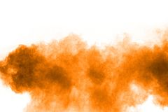 Orange color powder splatter on white background. Color particles splash. On transparent background stock photo