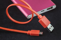 Orange color USB cable and red power bank Stock Photos