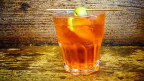 Orange colored alcoholic drink. A stable glass in front of a rustic wall, orange colored alcoholic drink inside. The drink is decorated with a piece of lemon and Stock Photo