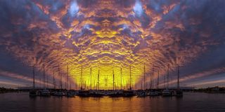 Orange colored altocumulus cloud, sunset seascape over marina. Spectactular non urban coastal , orange and yellow cloud, grey blue sky, sunset landscape. With royalty free stock images