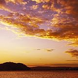 Orange colored Altocumulus cloud, sunset seascape. Sunset seascape photo art. Yellow and Orange coloured picturesque Altocumulus cloudy sky background scene stock photo