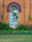 Orange colored bricks stone wall with big old grunge window covered with green metal grid, green grass floor, and plants at summer. Time, Montazah Public park Stock Photography