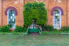 Orange colored bricks stone wall with two big old grunge windows and closed grunge door framed by two green bushes. Orange colored bricks stone wall with two big Royalty Free Stock Photos