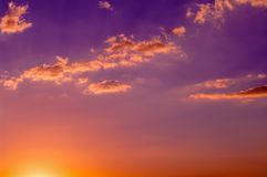Orange colored clouds on colorful sunset sky. Orange and purple color sky. Sun at horizon stock images