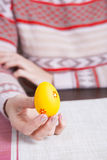 Orange colored easter egg in female hands Royalty Free Stock Images