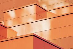 Orange colored geometric background of metal building facade. Abstract architectural shapes and lines royalty free stock photo