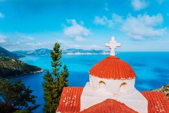 Orange colored Hellenic shrine Proskinitari on the cliff edge with defocused sea and cloudscape view in the background.  royalty free stock photography