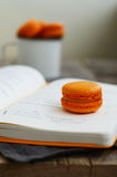 Orange colored macaroon cookie over open diary w. Orange colored mango and passion fruit macaroon cookie over open diary with notes Stock Images