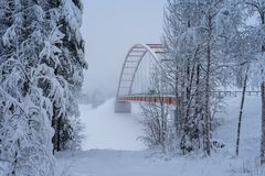 Orange colored suspension bridge crossing a river in northern Sweden. Arc shaped orange colored suspension bridge crossing a river in northern Sweden, ice and Stock Image