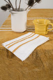 Orange-Colored Teacup and White Napkin on Orange-Colored Tablecl Stock Photos