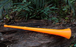 Orange colored vuvuzela. A plastic horn that produces a loud monotone note traditionally used at football matches in Africa stock photo