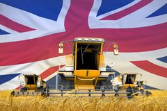 4 orange combine harvesters on wheat field with flag background, United Kingdom UK agriculture concept - industrial 3D