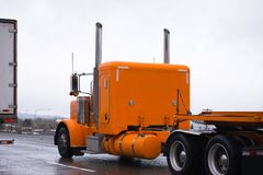 Orange big rig classic old style semi truck driving on highway i Stock Images