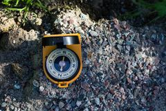 Orange compass with a mirror on the rocks shows the way to the tourist, space for text. Compass with a mirror on the rocks shows the way to the touris royalty free stock image