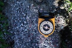 Orange compass with a mirror on the rocks shows the way to the tourist, space for text. Compass with a mirror on the rocks shows the way to the touris royalty free stock photo