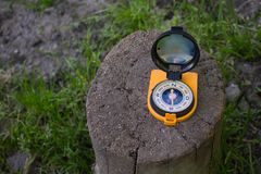 Orange compass on stump in the shady forest, shows the way. Orientation and travel concept. Orange compass on stump. Orientation and travel concept, space for stock photo