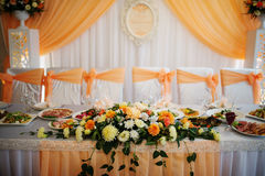 Orange composition of flowers on table of newlyweds. Royalty Free Stock Photography