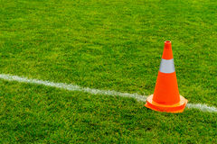 Orange cone on grass field Stock Photos