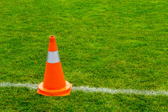 Orange cone on grass field Royalty Free Stock Images