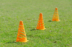 Orange cone markers on the green grass Stock Images