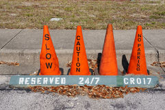 Orange cone (pylon) with no parking, slow and caution sign Royalty Free Stock Image