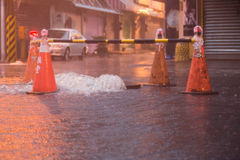 Orange cones around overflowing manhole Stock Images