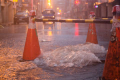 Orange cones around overflowing manhole Stock Image