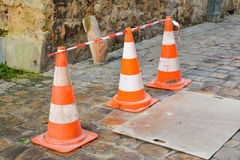 Orange cones on street. Orange cones on a medieval street in France stock image