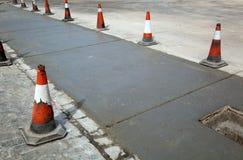 Orange cones on street repair. Rows of orange traffic cones next to a street repair Stock Images