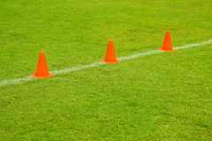 Orange cones on turf football or soccer green field, Training equipment. 