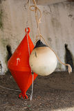 Orange conical buoy and white spherical buoy hanging outside wat Royalty Free Stock Image