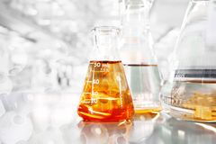 Orange so in conical three flasks with chemical structure in sci. Ence education laboratory background royalty free stock image