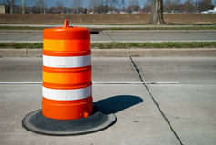 Orange construction barrel. A view of a bright orange construction barrel in the middle of a road or highway Royalty Free Stock Photos